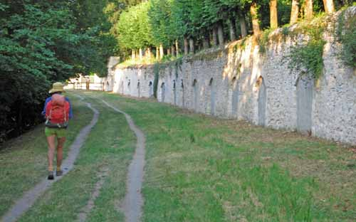 Walking in France: Château wall beside the Loire, with arched openings leading into the cliff