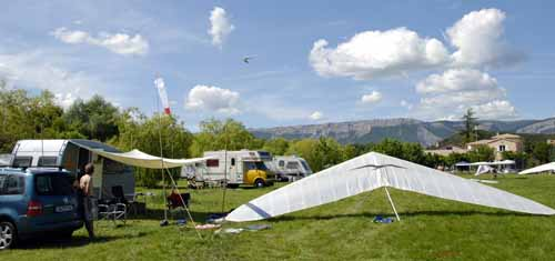 Walking in France: A distant hang-glider approaching the landing strip with a windsock in the foreground