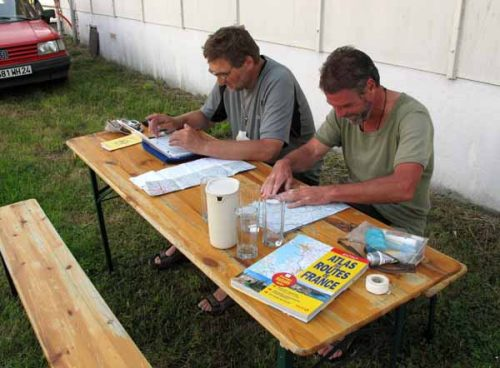 Walking in France: Peter doing his blog and Kees planning their route for tomorrow, outside the gite