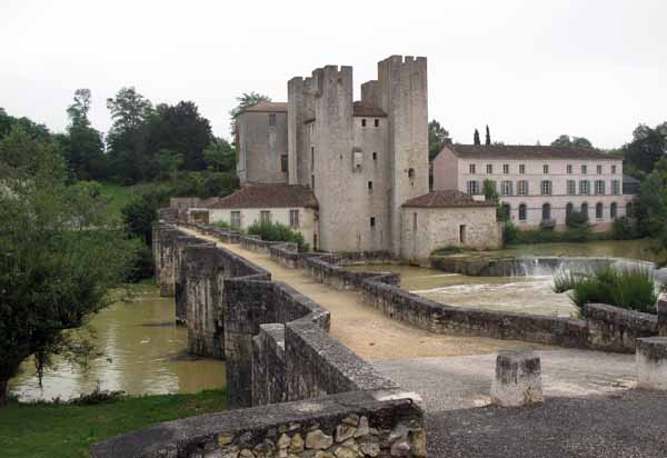 Walking in France: The oddly lop-sided mill building next to the foot bridge