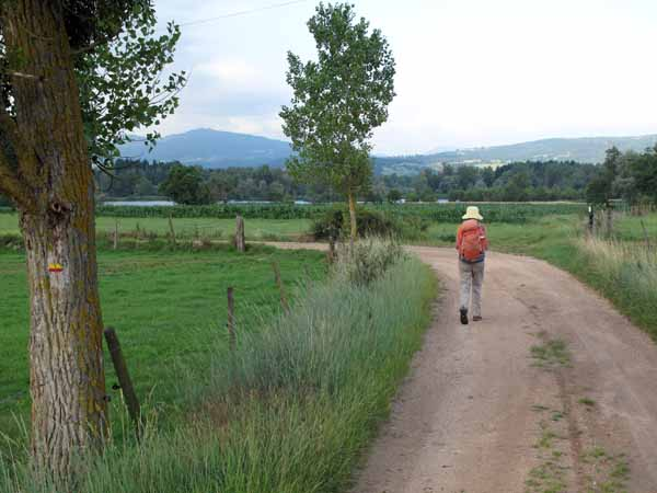 Walking in France: Passing through cultivated fields with the ponds of the gravel pits beyond