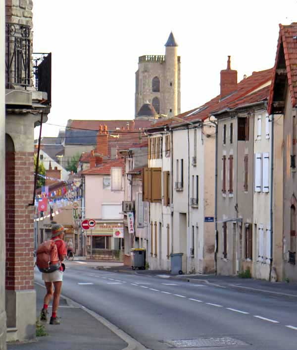 Walking in France: Heading back to the bar for breakfast, with the impressive clock tower looming over the town